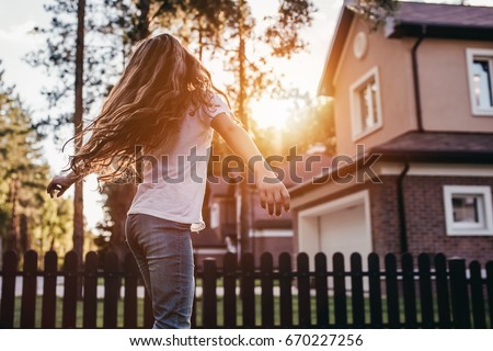 Pretty little girl is dancing and having fun on the backyard on the sunset.
