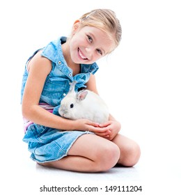 pretty little girl in denim clothing playing with white rabbit