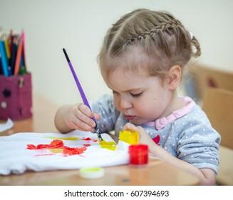 pretty little girl draws with paints, early development, creativity, kindergarten, indoor
