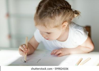 pretty little girl draws with pencils, early development, creativity, kindergarten, indoor