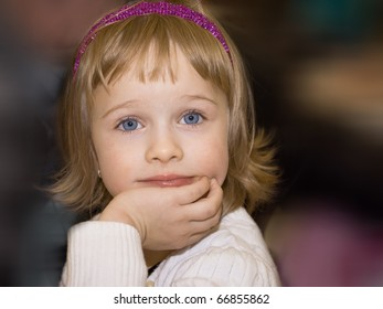 Pretty little girl dreaming portrait on the dark background.