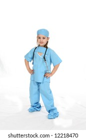 Pretty little girl dressed in medical scrubs with her hands on her hips.