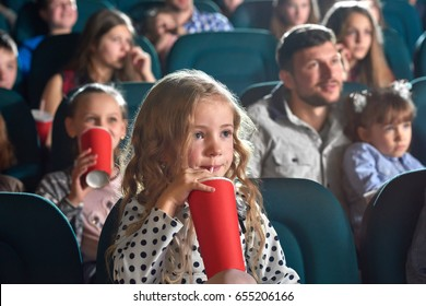 Pretty little girl drinking coke sitting at the movie theatre enjoying watching cartoon copyspace happiness positivity people leisure children child kids kid cuteness innocence entertainment activity.