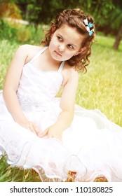 Pretty little girl  in fine dress sitting on the lawn
