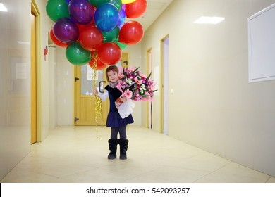 Pretty little girl with flowers and balloons stands in empty hallway of maternity hospital