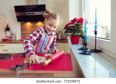 Pretty little girl with funny pigtails making christmas cookies in different forms in modern kitchen