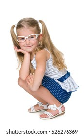 A pretty little girl in glasses is sitting against the white background