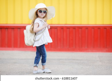 Pretty little girl in hat and sunglasses hanging backpack going for vacation holidays, summer, vacation, travel concept. smiling cute little girl on beach vacation.