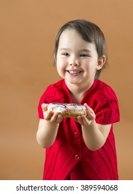 Pretty little girl holding donuts at brown background in studio