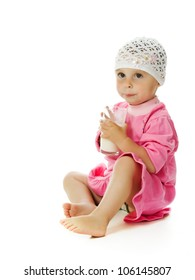 A pretty little girl is holding a glass of milk; isolated on the white background