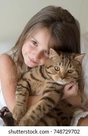 Pretty little girl holding her cat