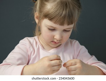 Pretty little girl holding a needle, grey background