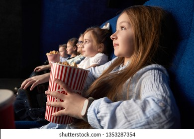 Pretty, little girl holding popcorn bucket, sitting with friends in cinema, in comfortable chairs. Children watching cartoon or movie. Leisure, entertainment.