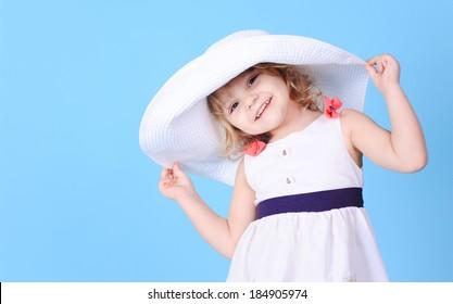Pretty little girl holding summer hat on blue
