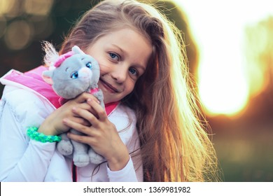 pretty little girl hugging a favorite stuffed animal - a cat for