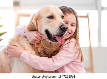 Pretty little girl hugging golden retriever dog and smiling. Portrait of friendship