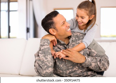 pretty little girl hugging her military father