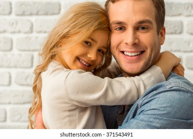 Pretty little girl hugging her beautiful young father, looking in camera and smiling while standing against white brick wall