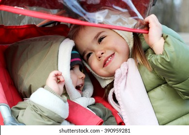 Pretty little girl hugs his cute toddler brother sitting in the stroller in the park at first sunny spring day, happy family weekend