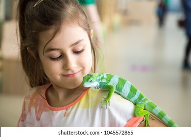 Pretty little girl with iguana reptile in a zoo