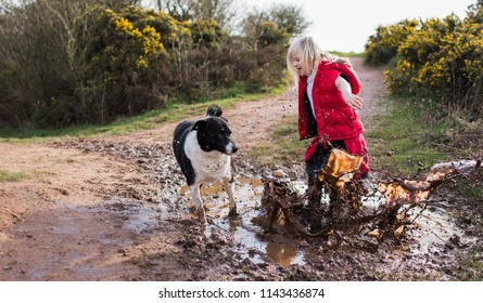 Pretty little girl jumping in very muddy puddle playing with her pet dog in the cold autumn weather in Stoke on Trent, Staffordshire