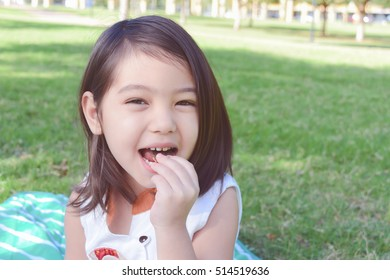 a pretty little girl laughing and eating cookie in green park, filtered tones