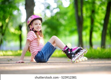 Pretty little girl learning to roller skate outdoors on beautiful summer day