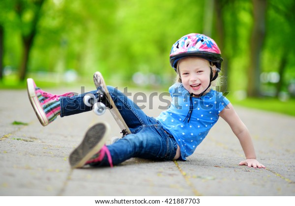Pretty little girl learning to skateboard outdoors on beautiful summer day