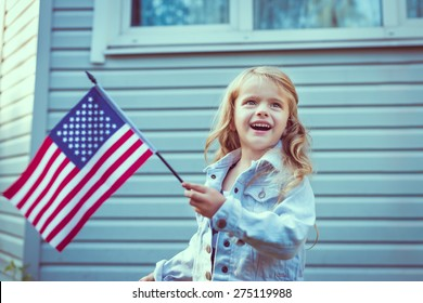 Pretty little girl with long curly blond hair smiling and waving american flag. Independence Day, Flag Day concept. Vintage and retro toning. Instagram filters