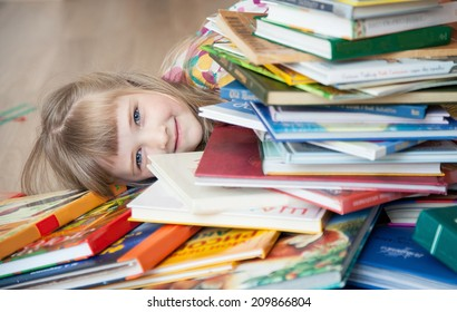 Pretty little girl lying on the floor among books