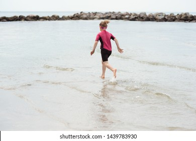 Pretty little girl in neopren swimsuit running an playing with waves in Baltic sea