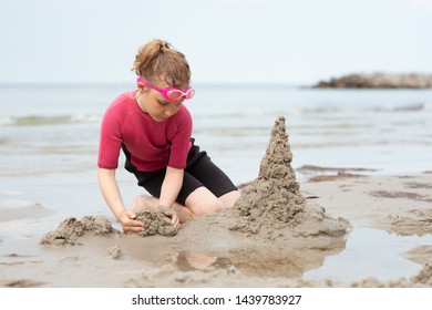 Pretty little girl in neoprene swimsuits playing with sand in a Baltic sea