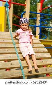 Pretty little girl on outdoor playground equipment