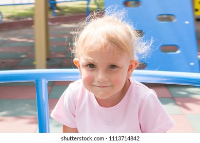 A pretty little girl on the playground.