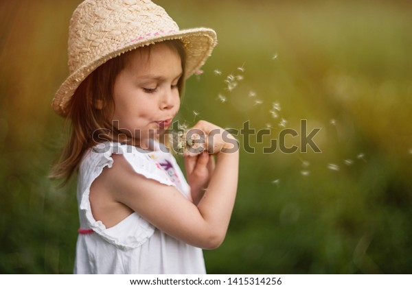 А pretty little girl on a straw hat is blowing on a dandelion. Dandelion fluff is flying. Summer sunny child is holding a flower. Dundelion focus.