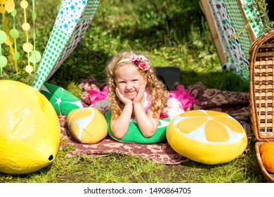 Pretty little girl with picnic basket sitting in meadow in a tent