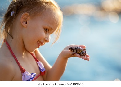 Pretty little girl with pigtails in swimsuit holding a frog. Nature and children.
