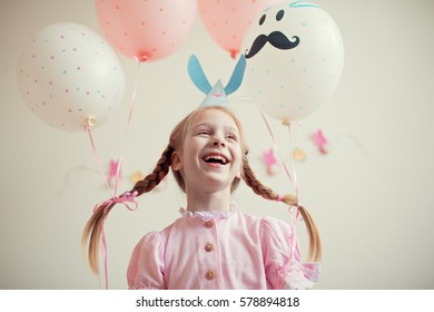 Pretty little girl in a pink dress and cap Bunny rabbit with balloons on the pigtails laughs. Childhood. Easter. The occasion.