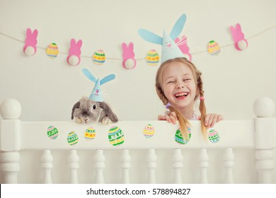 Pretty little girl in a pink dress and cap with a rabbit laugh. The occasion. Easter. Childhood.