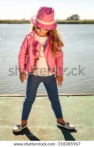 4863fa0603e Pretty little girl in pink leather jacket and fedora hat standing with her  head tilted down