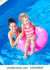 Pretty little girl in an pink life preserver with her mother in swimming pool outdoors. Vertical view.
