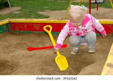 Pretty little girl play on playground in the park - outdoor portrait.
