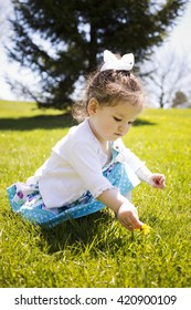 pretty little girl playing in the grass during summer