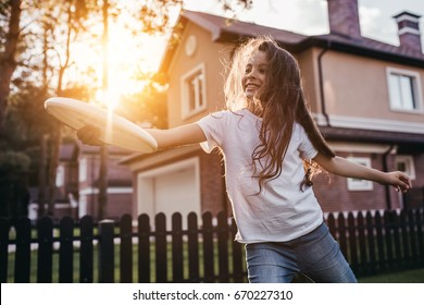 Pretty little girl is playing, having fun and smiling on the backyard on the sunset.