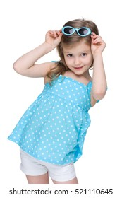 A pretty little girl in a polka dot blue dress on the white background