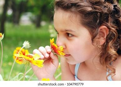 Pretty little girl portrait smelling yellow flower