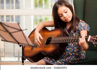Pretty little girl practicing some new sound on a guitar at home