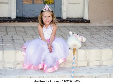 Pretty little girl in a Little princess costume poses on the porch steps with her unicorn stick horse