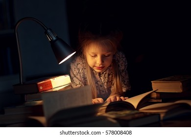 A pretty little girl reading a book on the floor under the lamp. Children and education.