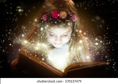 Pretty little girl reading magic book